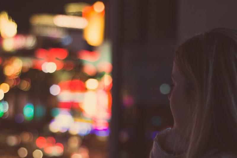 Девушка грустит и смотрит в окно на ночной город